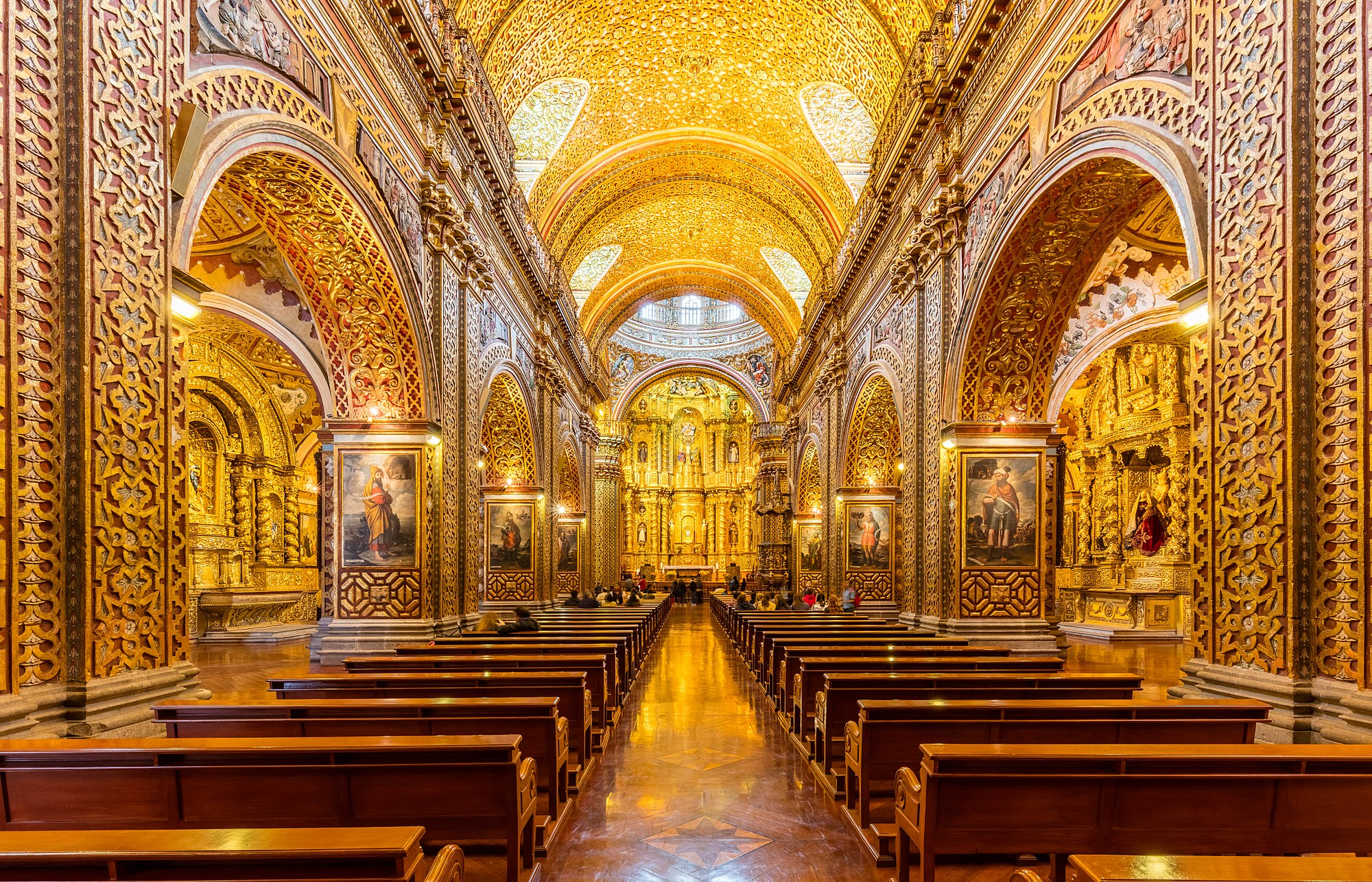 Main nave of the Church of the Society of Jesus (La Iglesia de la Compañía de Jesús), a Jesuit church in Quito, Ecuador. The exterior doesn't give an idea of the beauty of the interior, with a large central nave, which is profusely decorated with gold leaf, gilded plaster and wood carvings, making of it the most ornate church in Quito. The temple is one of the most significant works of Spanish Baroque architecture in America and considered the most beautiful church in Ecuador.