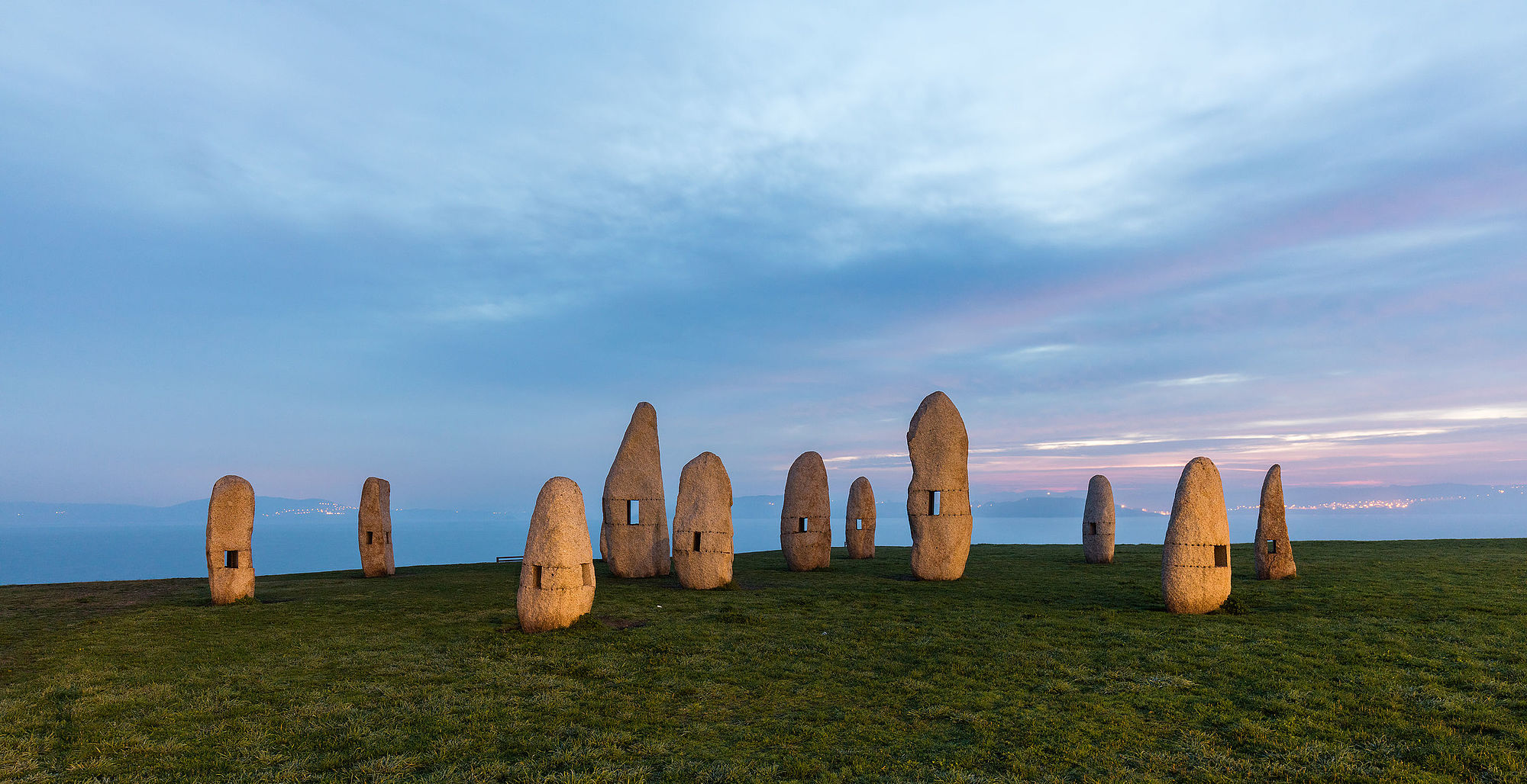 Family of Menhirs, Tower Park, La Coruña, Spain. The sculpture group, created in 1994, is work of artist Manolo Paz. The holes in the rocks are designed to frame different views of the park and the bay through them.