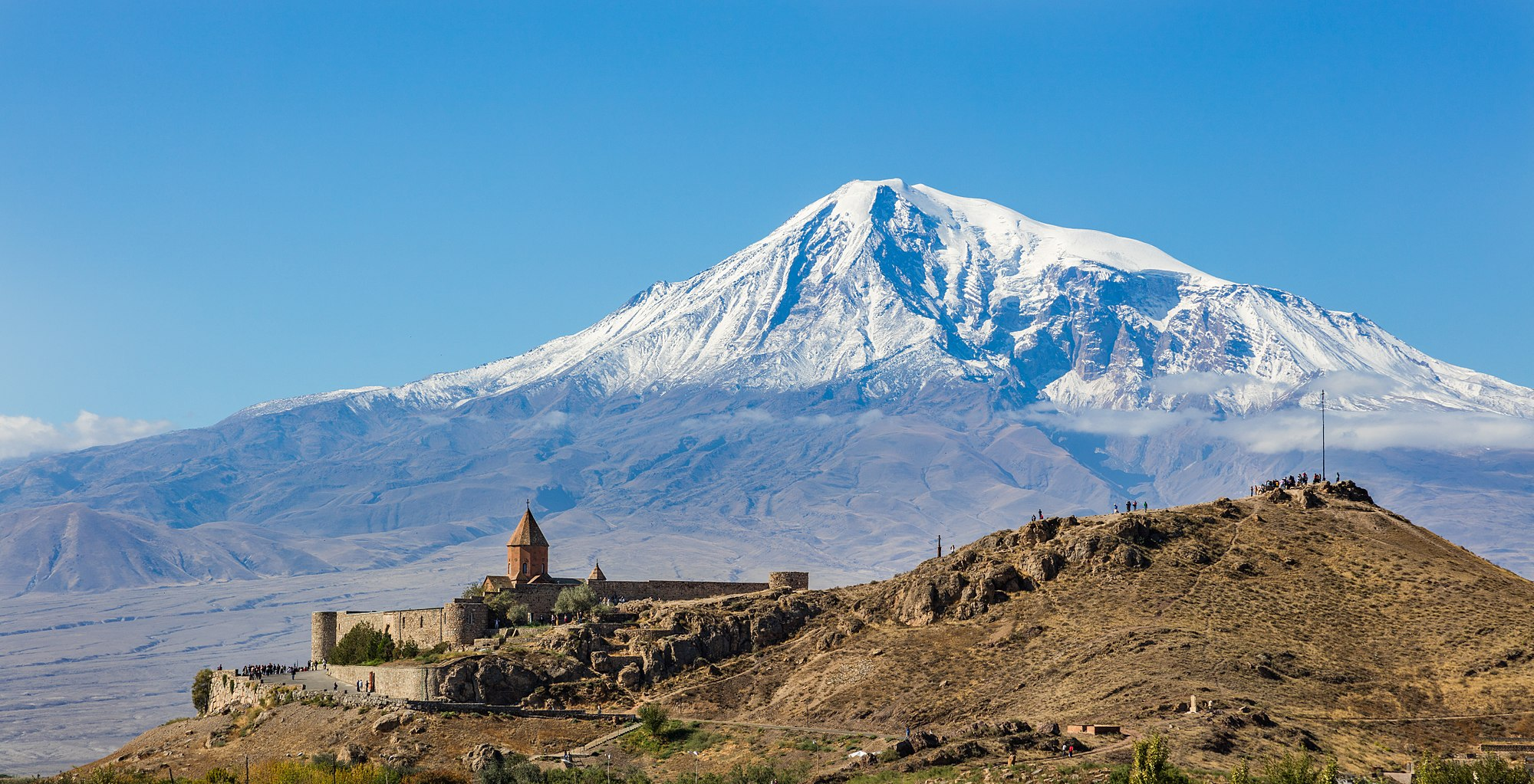 View of Khor Virap, an Armenian monastery and one of the most visited pilgrimage sites in Armenia located in the Ararat plain with the Mount Ararat in the background. Khor Virap's notability as a monastery and pilgrimage site is due to the fact that Gregory the Illuminator, religious leader who converted Armenia from paganism to Christianity in 301, becoming the first nation to adopt Christianity as its official religion, was initially imprisoned here for 14 years by King Tiridates III of Armenia. A chapel was initially built in 642 by Nerses III the Builder as a mark of veneration to Saint Gregory. Over the centuries, it was repeatedly rebuilt and the current appearance dates from 1662.