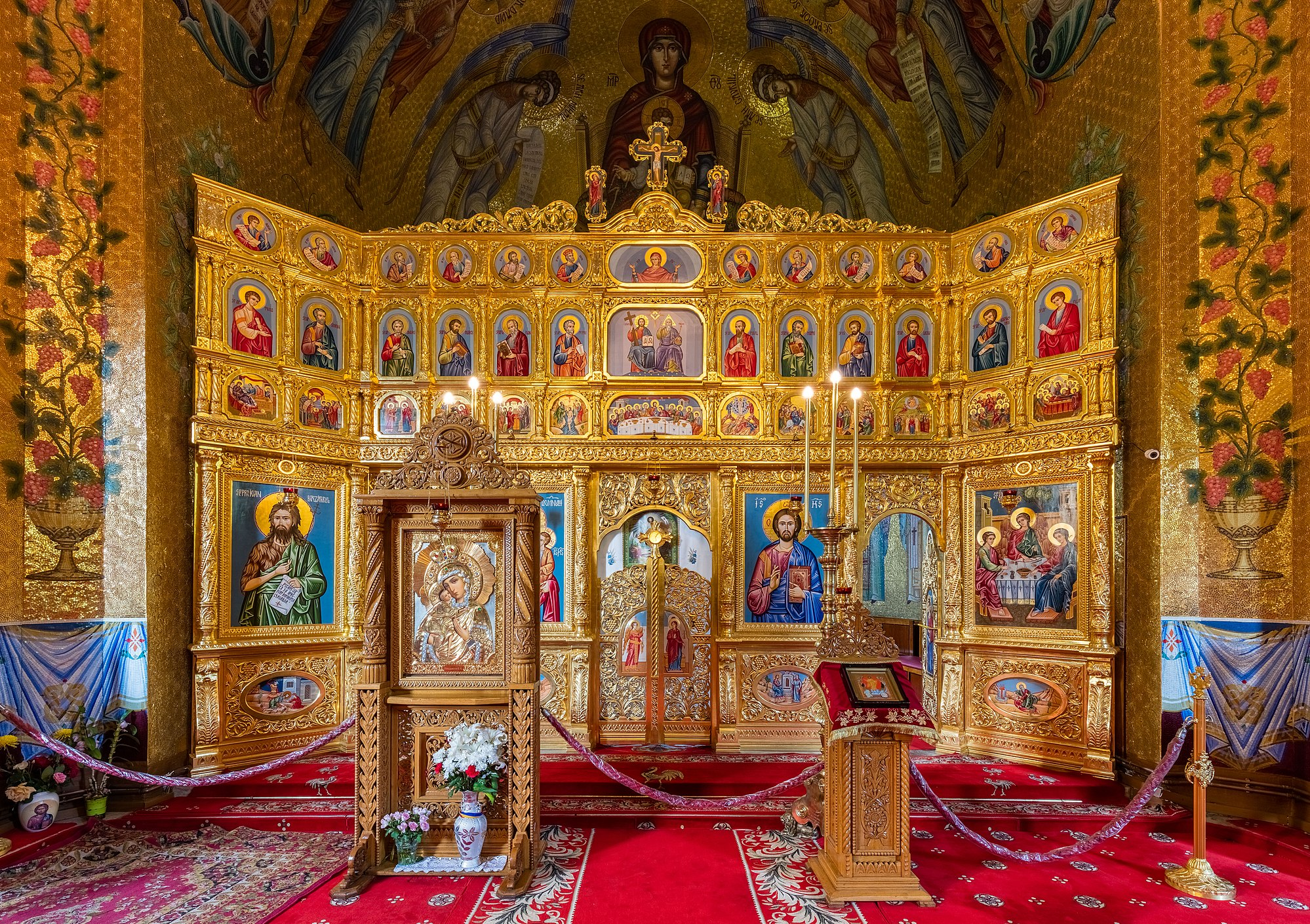 Iconostasis in the church of the Cocoș Monastery, Romania. The monastery, located in a forest clearing 6 kilometres (3.7 mi) from Niculițel, was built between 1883 and 1913 and is dedicated to the Dormition of the Theotokos.