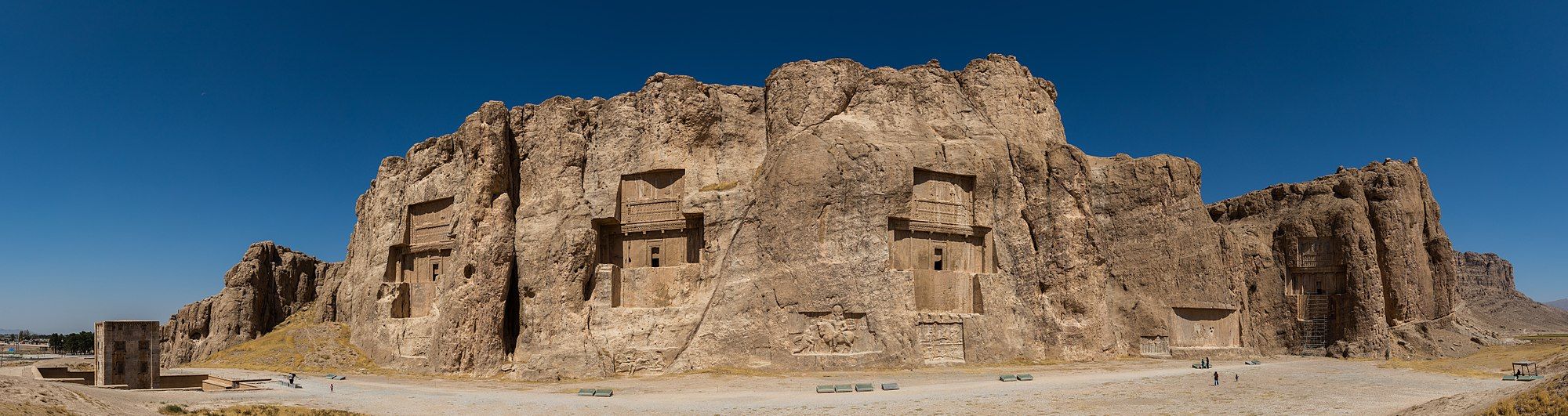 Panoramic view of the ancient Naqsh-e Rustam necropolis located about 12 km northwest of Persepolis, in Fars Province, Iran. The site includes rock reliefs of Achaemenid and Sassanid periods, 4 tombs of Achaemenid kings and a Cube of Zoroaster (far left). The reliefs are the oldest elements (the oldest one from 1000 BC) of Elamite origin. The tombs were carved out of the rock and belong (left to right) to Darius II (c. 423-404 BC), Artaxerxes I (c. 465-424 BC), Darius I (c. 522-486 BC) and Xerxes I (c. 486-465 BC). The Cube of Zoroaster belongs to the Achaemenid era (5th century BC) and its purpose is still unclear.