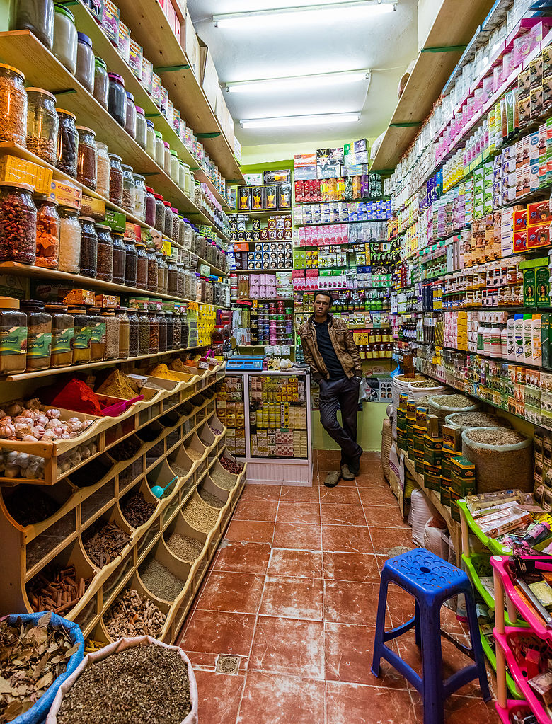 Seller posing in a grocery and cosmetics shop in Grand Socco, Tangier, Morocco.