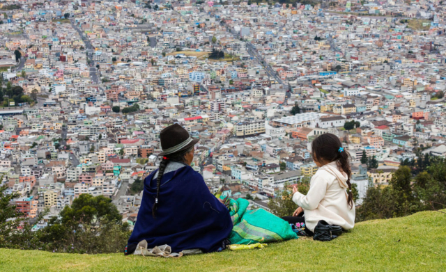 Indigenous people peeling maize while overlooking Quito from El Panecillo, Ecuador.