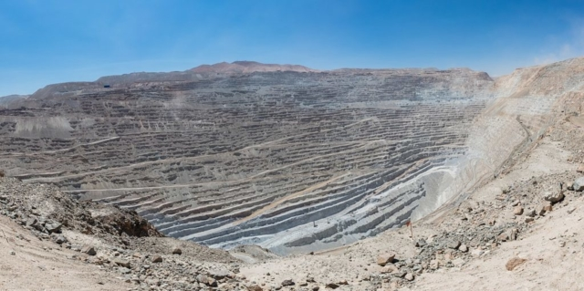 Panoramic view of Chuquicamata, a state-owned copper mine located at 2,850 metres (9,350 ft) above sea level just outside Calama, north of Chile. It is by excavated volume the largest open pit copper mine in the world. The huge hole was started in 1882 as a mine to extract gold and copper. It is 4.5 kilometres (2.8 mi) long, 3.5 kilometres (2.2 mi) wide and with a depth of 850 metres (2,790 ft) it is the second deepest open-pit mine in the world (after Bingham Canyon Mine in Utah, USA). Note: to get a feeling of the scale spot out a haul truck, which is 9.5 metres (31 ft) long and 4.5 metres (15 ft) high.