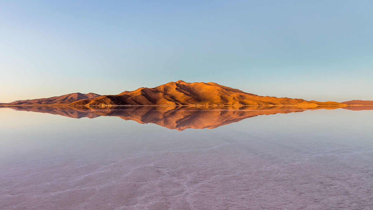 Mountains and reflections surrounding the Uyuni salt flat during sunrise, Bolivia.