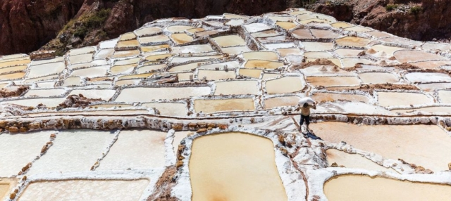 Worker carrying a sack of salt on his shoulder in Salineras (salt evaporation ponds) in Maras, Peru.