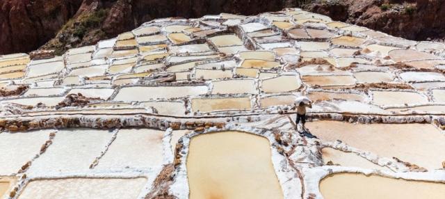 Worker carrying a sack of salt on his shoulder in Salineras (salt evaporation ponds) in Maras, Peru.