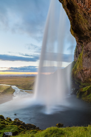 Lateral view of the Seljalandsfoss waterfall during a sunset, Suðurland, Iceland.